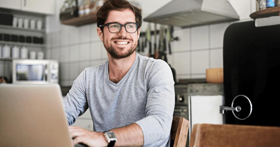 dueño de negocio sonríe frente a laptop